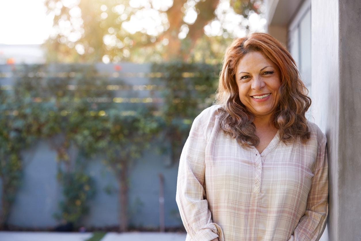 Portrait Of Smiling Senior Hispanic Woman In Garden At Home Against Flaring Sun