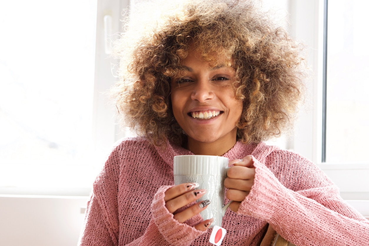 Portrait of smiling young woman with cup of tea